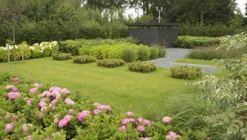 Moderne tuin met verhoogde vijver en golfgreen